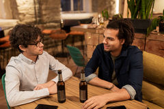 Happy male friends drinking beer at bar or pub. People, men, leisure, friendship and communication concept - happy male friends drinking bottled beer and talking stock images