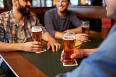 Happy male friends drinking beer at bar or pub. People, men, leisure, friendship and communication concept - close up of happy male friends drinking draft beer Stock Images