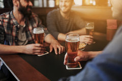 Happy male friends drinking beer at bar or pub. People, men, leisure, friendship and communication concept - close up of happy male friends drinking draft beer royalty free stock photography