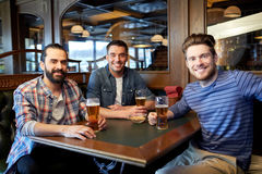 Happy male friends drinking beer at bar or pub. People, men, leisure, friendship and communication concept - happy male friends drinking draft beer at bar or pub royalty free stock images