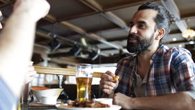 Happy male friends drinking beer at bar or pub. People, men, leisure, friendship and communication concept - happy male friends drinking beer and eating bread stock video