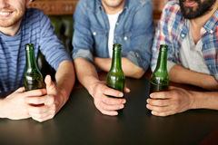 Happy male friends drinking beer at bar or pub. People, men, leisure, friendship and communication concept - group of happy male friends drinking beer at bar or stock photos