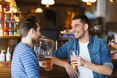 Happy male friends drinking beer at bar or pub. People, men, leisure, friendship and communication concept - happy male friends drinking beer and talking at bar royalty free stock images