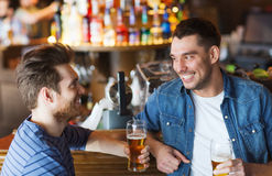 Happy male friends drinking beer at bar or pub. People, men, leisure, friendship and communication concept - happy male friends drinking beer and talking at bar royalty free stock photos