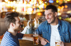 Happy male friends drinking beer at bar or pub. People, men, leisure, friendship and communication concept - happy male friends drinking beer and talking at bar royalty free stock photo