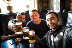 Happy male friends drinking beer and taking selfie with smartphone at bar or pub. Male friends drinking beer and taking selfie with smartphone at bar or pub Stock Photos
