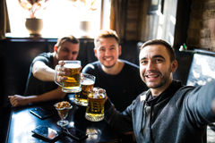 Happy male friends drinking beer and taking selfie with smartphone at bar or pub. Male friends drinking beer and taking selfie with smartphone at bar or pub Royalty Free Stock Photography