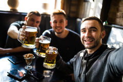 Happy male friends drinking beer and taking selfie with smartphone at bar or pub. Male friends drinking beer and taking selfie with smartphone at bar or pub Royalty Free Stock Photos
