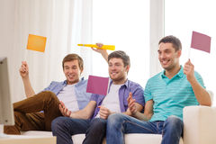 Happy male friends with flags and vuvuzela Stock Images