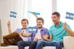 Happy male friends with flags and vuvuzela Royalty Free Stock Photo