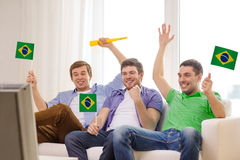 Happy male friends with flags and vuvuzela. Friendship, sports and entertainment concept - happy male friends with flags and vuvuzela supporting football team at stock images