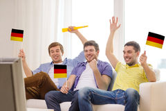 Happy male friends with flags and vuvuzela Royalty Free Stock Images