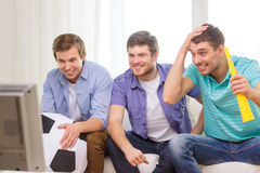 Happy male friends with football and vuvuzela Royalty Free Stock Images