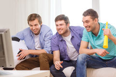 Happy male friends with football and vuvuzela Royalty Free Stock Photography