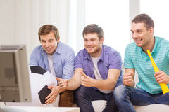 Happy male friends with football and vuvuzela Stock Photo