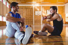 Happy male friends practicing stretching exercise. While sitting on floor in court Royalty Free Stock Photo