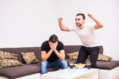 Happy male friends supporting football team at home. One man happy, another sad. Friendship, sports and entertainment concept - happy male friends supporting Royalty Free Stock Image