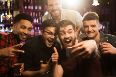 Happy male friends taking selfie and drinking beer. At bar or pub royalty free stock photos