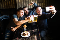 Happy male friends taking selfie and drinking beer at bar or pub on party. People, leisure, friendship, technology and party concept - happy male friends taking Royalty Free Stock Photo