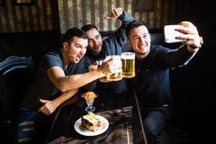 Happy male friends taking selfie and drinking beer at bar or pub. People, leisure, friendship, technology and party concept - happy male friends taking selfie Stock Photography