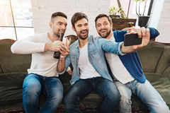 Happy male friends taking a selfie. Moment to remember. Happy positive smiling male friends posing for a photo and looking at the camera while taking a selfie Royalty Free Stock Images