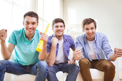 Happy male friends with vuvuzela Stock Images