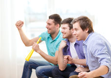 Happy male friends with vuvuzela watching sports Stock Image