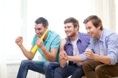 Happy male friends with vuvuzela watching sports Stock Photo