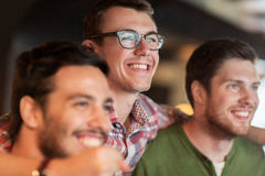 Happy male friends watching football at bar or pub. People, leisure and friendship concept - happy male friends watching sport game or football match at bar or Royalty Free Stock Photography