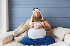 Happy male glutton enjoying sweet food. Carefree thick guy is eating zephyr with enjoyment. He is sitting on couch with closed eyes stock images