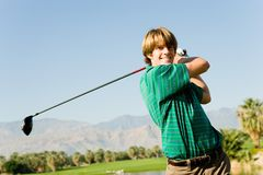 Happy Male Golfer Swinging Golf Club Royalty Free Stock Image