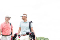 Happy male golfers communicating against clear sky Stock Image