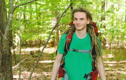 Happy male hiker with backpack. Trekking through the forest Royalty Free Stock Photography
