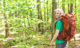 Happy male hiker with backpack. Trekking through the forest Stock Images
