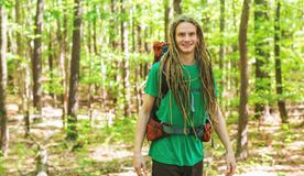 Happy male hiker with backpack. Trekking through the forest Royalty Free Stock Image