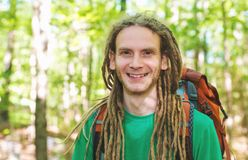 Happy male hiker with backpack. Trekking through the forest Stock Image