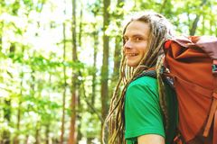 Happy male hiker with backpack. Trekking through the forest Royalty Free Stock Photo