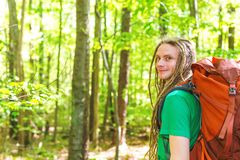 Happy male hiker with backpack. Trekking through the forest Stock Photo
