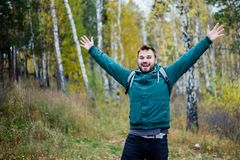Happy male hiker has raised his hands in success royalty free stock photography