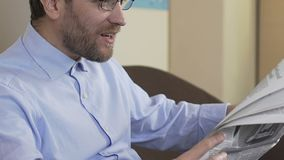 Happy male in his 40s sitting on sofa and reading horoscope in newspaper, press. Stock footage stock video