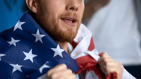 Happy male holding American flag, watching sports competition, cheering team. Stock photo stock images