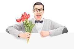 Happy male holding flowers behind a panel Royalty Free Stock Photo