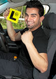 Happy male learner driver. Happy male driver holding L learner plates and sitting in a car stock image