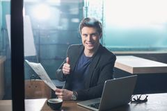 Happy male looking showing ok symbol. Portrait of beaming young man demonstrating thumb up gesture while reading newspaper. He situating at table in room. Relax Stock Photos