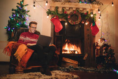 Happy male makes a purchase on the Internet via a laptop. Man in red sweater sitting in front of the fireplace. Guy on the background of Christmas tree and stock image