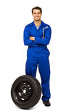 Happy Male Mechanic With Spare Tire. Full length portrait of happy male mechanic with spare tire over white background. Vertical shot Stock Photo