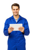 Happy Male Mechanic Using Digital Tablet. Over white background. Vertical shot Royalty Free Stock Images
