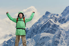 Happy male mountain climber with arms raised above the head. In the background the high mountains. Royalty Free Stock Photography
