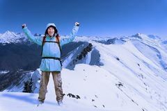 Happy male mountain climber with arms raised above the head. In the background the high mountains. Royalty Free Stock Images