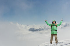 Happy male mountaineer man with raised arms. In background high mountains above clouds . Royalty Free Stock Photography